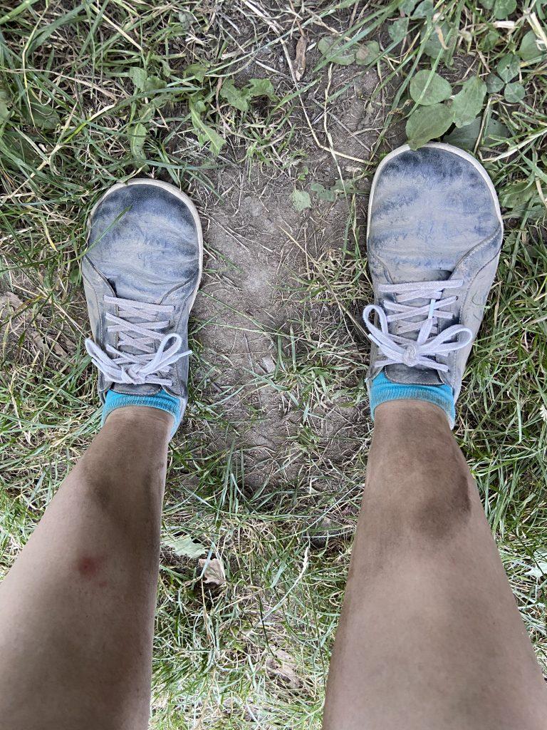 Blick hinunter auf schmutzige Beine und ehedem schwarze, schmutzige Schuhe.