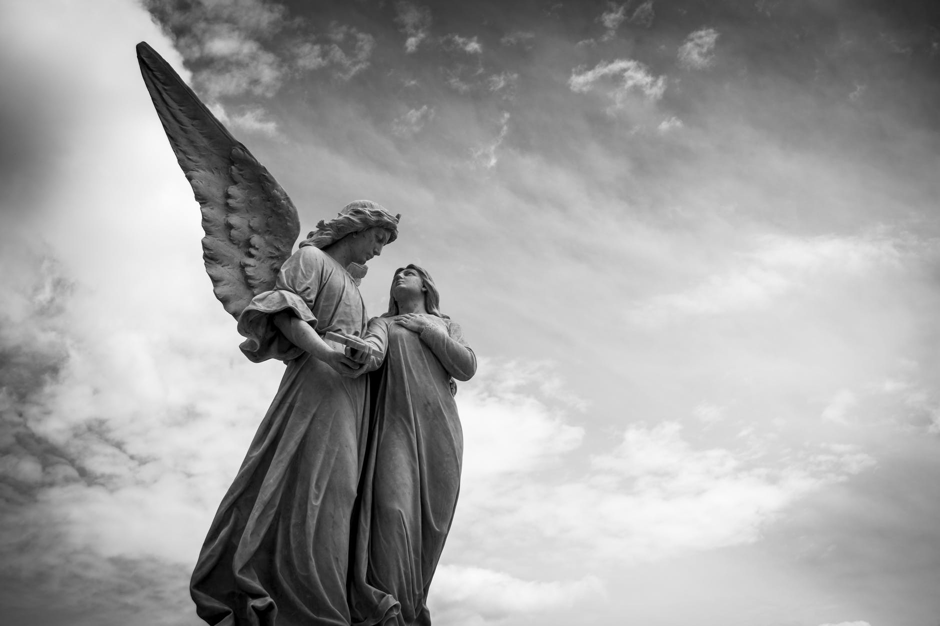 Engelstatue nebst Frau vor Wolken, Bild in Schwarz-Weiß.