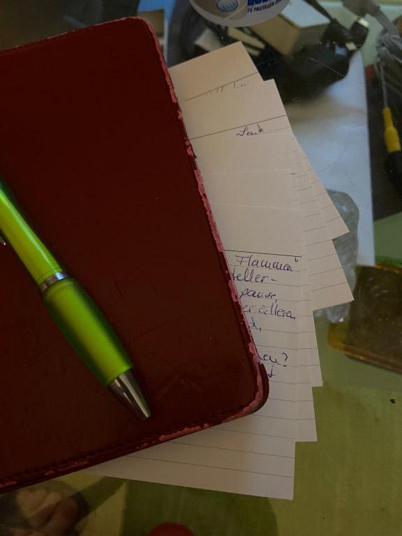 Einige beschriftete Karteikarten, aufgefächert, von einem Kindle verdeckt, darauf der gelbe Kugelschreiber von vorhin. Im Hintergrund Chaos, denn die Karten liegen auf einem Glastisch.