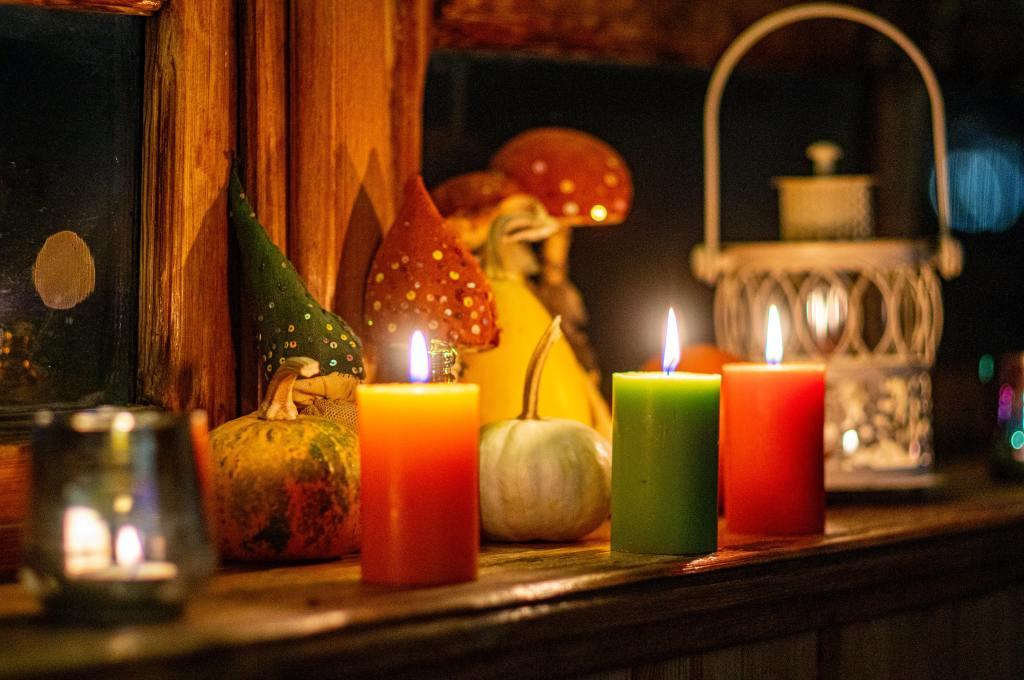 Zwei orange und in der Mitte eine grüne Stumpenkerzen auf einem hölzernen Sims, im Hintergrund etwas herbstliche Deko mit kleinen Kürbissen und Pilzen und Pailletten.