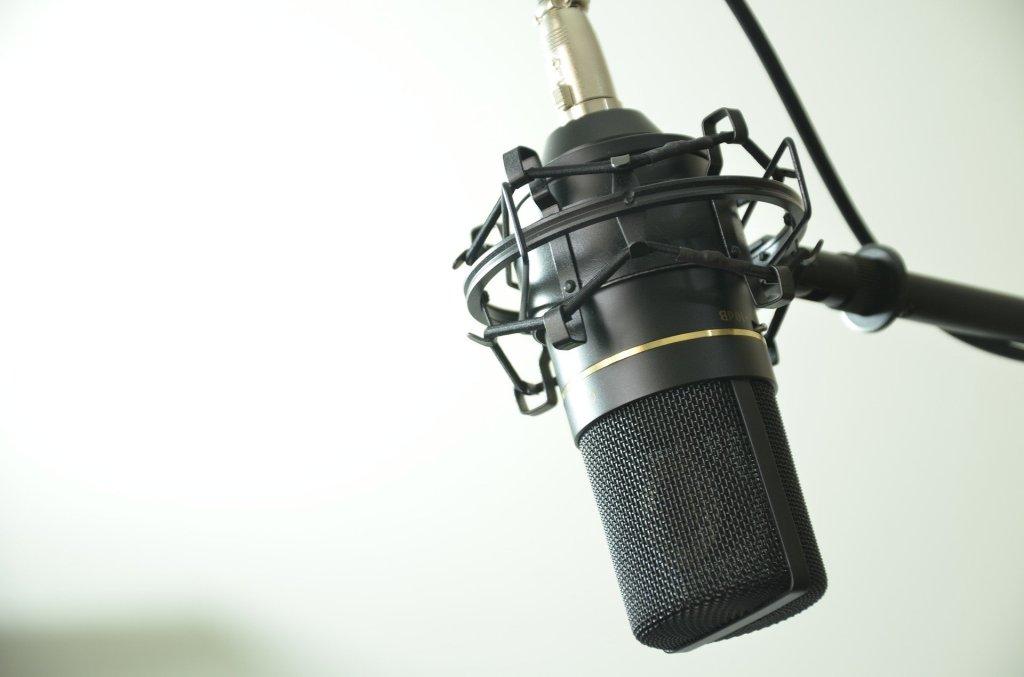 Heller Hintergrund, davor ein Prof-Mikrofon auf der rechten Bildseite.