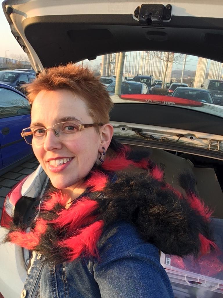 Selfie auf dem Parkplatz, vor dem geöffneten Kofferraum. Autorin mit kurzen roten Haaren und Brille, gekleidet in eine dunkelblaue Jeansjacke und eine gigantische rotschwarze Stoffspinne. Es könnte schlimmer sein.
