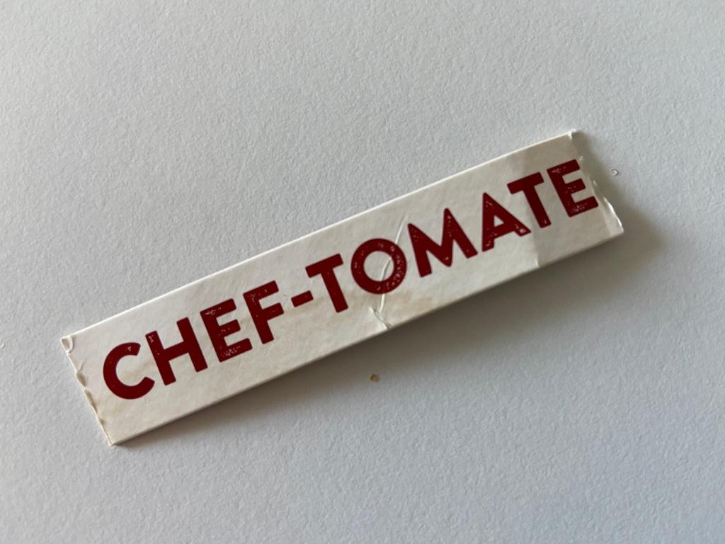 Weißer Hintergrund, darauf ein Pappschnipsel mit der Aufschrift CHEF-TOMATE.