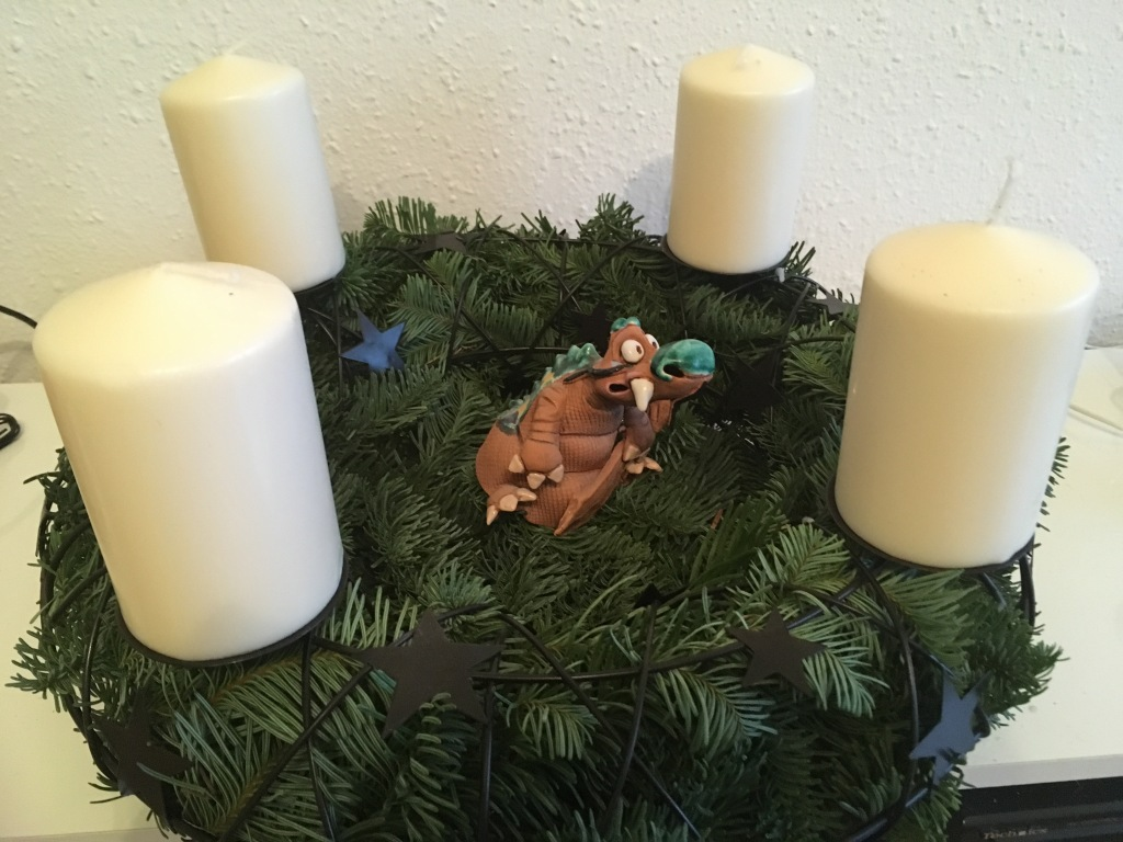Adventskrank aus Tannengrün in einem Metallkranz mit vier weißen Kerzen. In der Mitte sitzt ein Drache aus Ton.