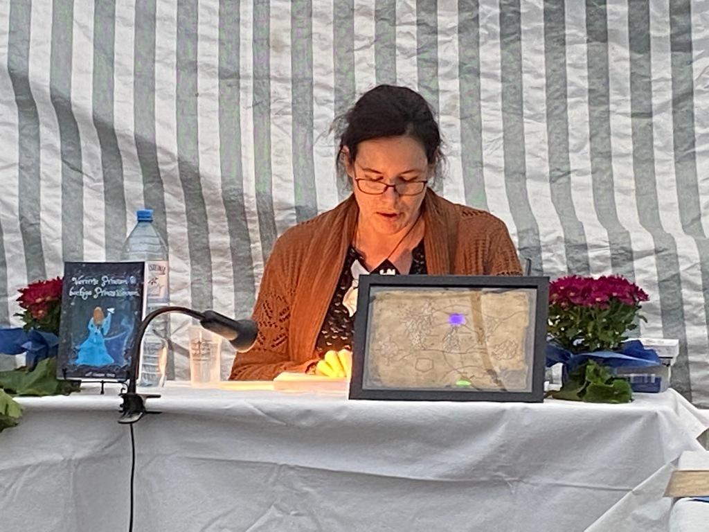 Tisch mit Buch, Landkarte und Blümchen als Deko, dahinter vorlesende Person mit Buch.