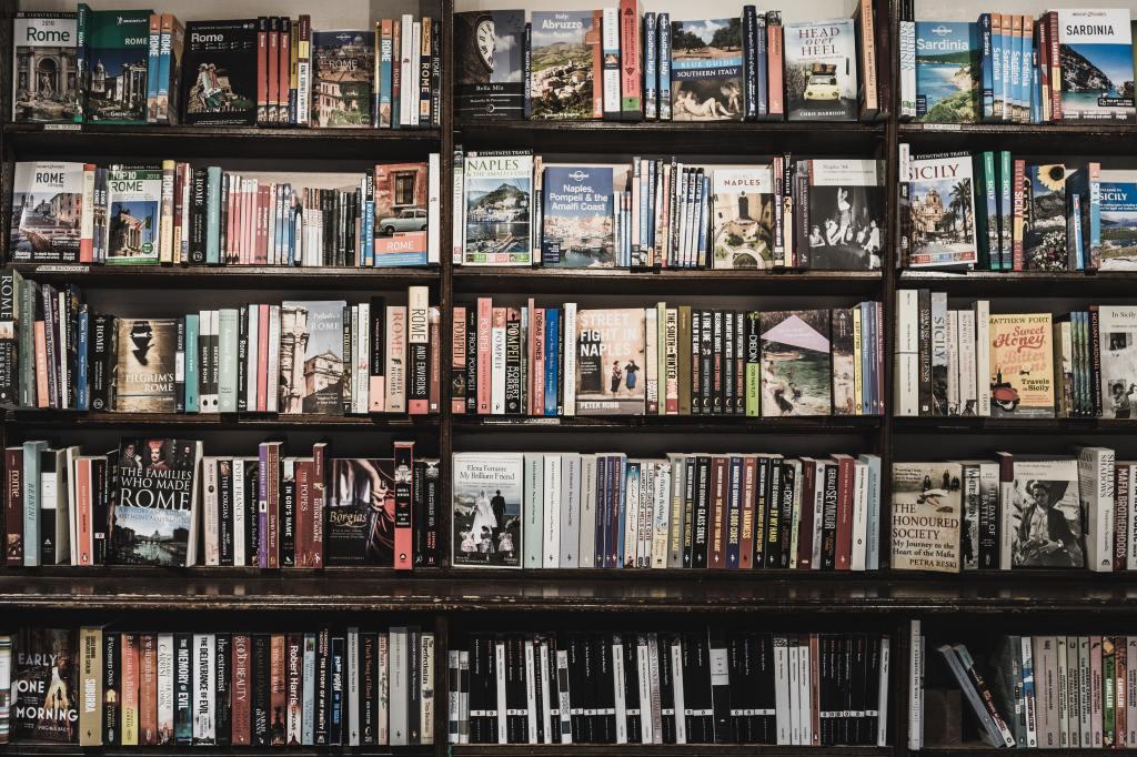 Ein dicht gepacktes Bücherregal mit vielen verschiedenen ordentlich aufgestellten englischsprachigen Titeln, überwiegend Taschenbücher.