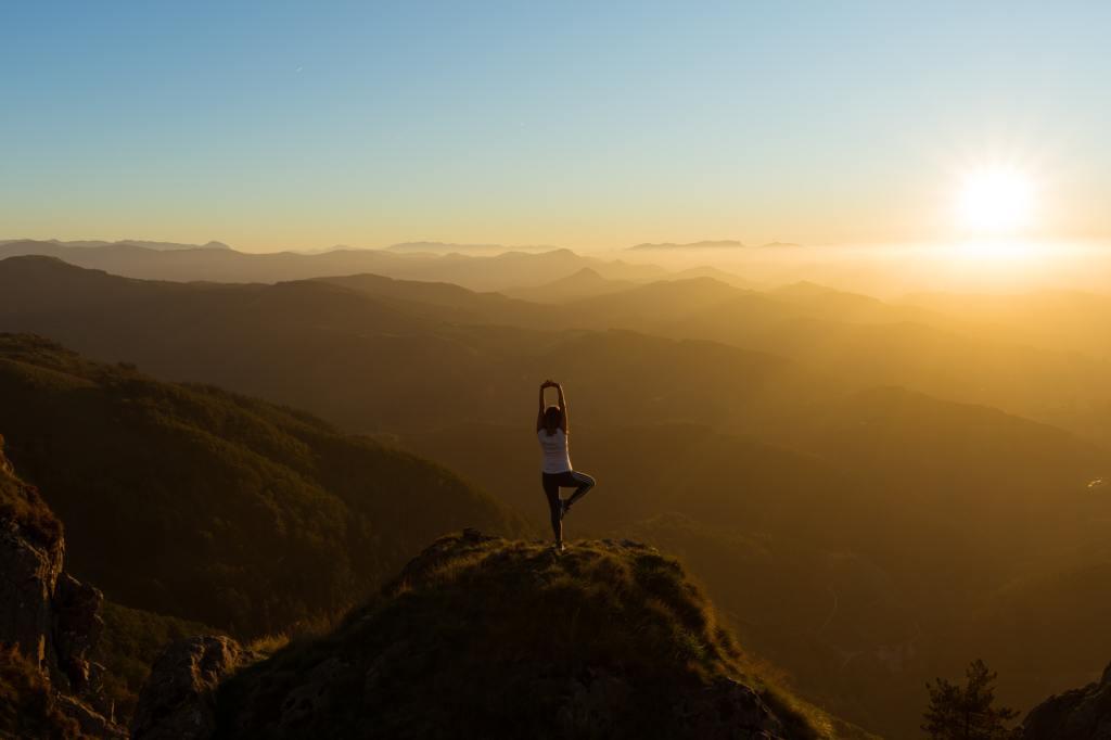 """Berggipfel bis zum Horizont, Sonnenaufgang, im Vordergrund steht eine Person mit dem Rücken zum Fotograf in der Yoga-Pose """"Baum"""" auf einem Gipel."""