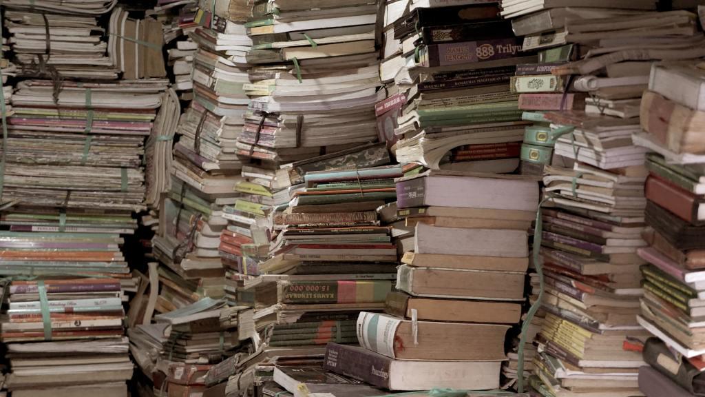 Unzählige abgegriffene Bücher, dicht an dicht und von unten nach oben gestapelt, mit Schnur zusammengehalten.