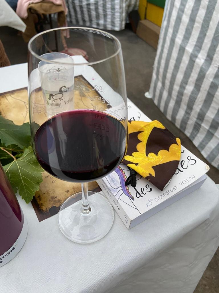 """Ein Glas Rowein auf einem Tisch, neben dem Buch """"Andrea die Lüsterne und die lustigen Tentakel des Todes"""", halb verdeckt von einem Mundnasenschutz mit Fledermausaufdruck."""
