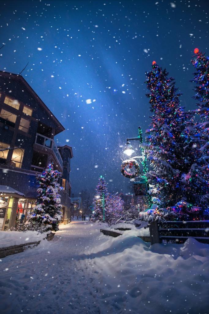 Winterliches Dorf bei Nacht: Links einige mehrstöckige Gebäude mit Beleuchting, rechts ein bunt blikender Tannenbaum. Der Boden ist schneebedeckt, neuer Schnee fällt von oben, der Himmel ist nachtblau.