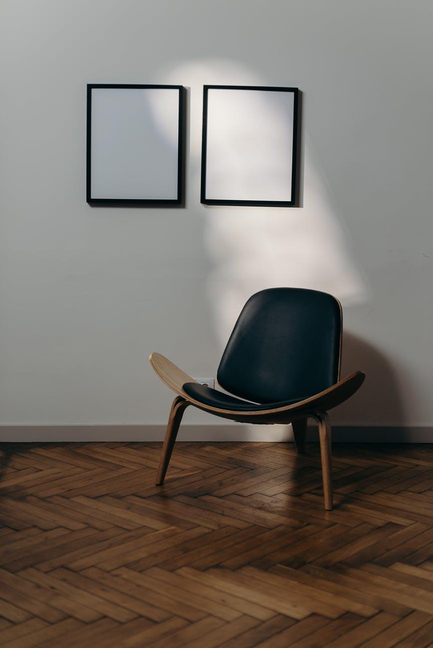 Schwarzbrauner Stuhl vor weißer Wand mit zwei leeren Bilderrahmen.