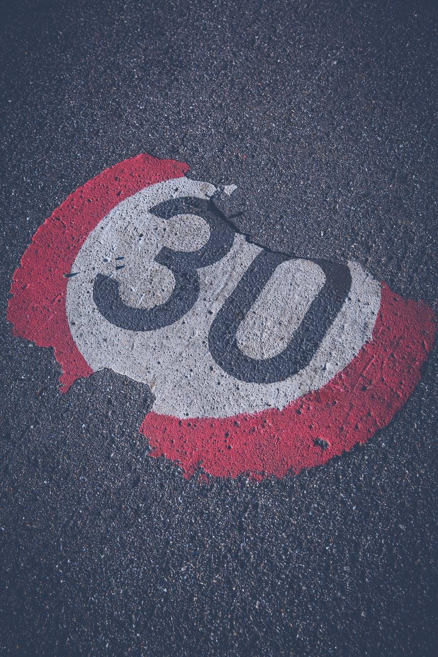 """Abblätterndes """"Tempo 30"""" Schild, auf die Fahrbahn gemalt."""