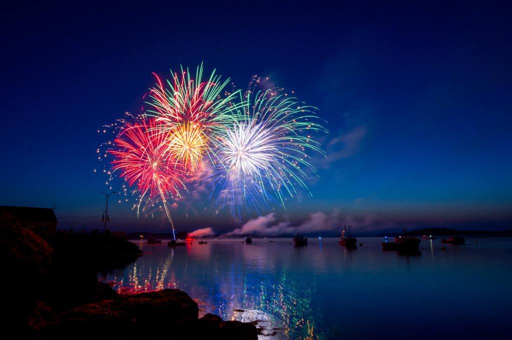 Über einer glatten, spiegelnden Wasserfläche bei Nacht explodiert Feuerwerk. Einige Boote liegen im Wasser. Der Himmel ist klar.