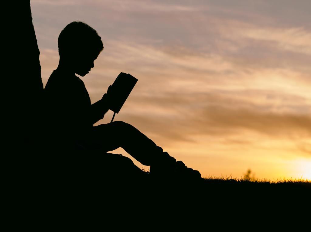 Himmel mit Abendstimmung, Violett- und Goldtöne. Davor im Scherenschnitt-Profil ein lesendes Kind, das sitzend sich an einen Buamstamm lehnt.