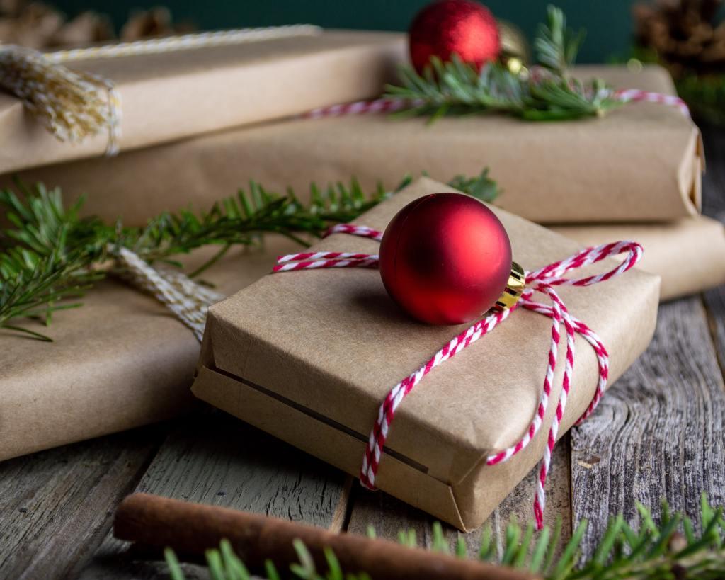 Mehrere in naturbraunes Packpapier verpackte Päckchen auf Holzbrettern, dekoriert mit rotweißer Schnur, roten Baumkugeln und Tannenzweigen.