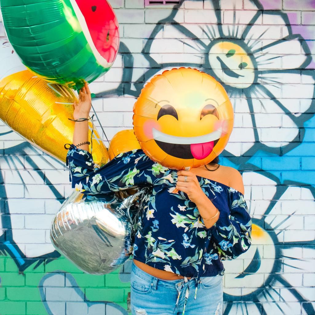 Vor einer mit Blumengrafitti besprühten Backsteinwand steht eine Frau mit dunkelblauem, geblümtem Oberteil. Ihr Kopf ist hinter einem Luftballon in Lach-Smilie-Form verborgen. Sie hält mehrere andere Ballons.