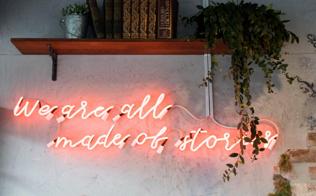 """An einer weiß verputzten Wand prangt als Neonschrift der Schriftzug: """"We are all made of stories."""" Darüber ein Regalbrett mit einigen Büchern und zwei Pflanzen."""