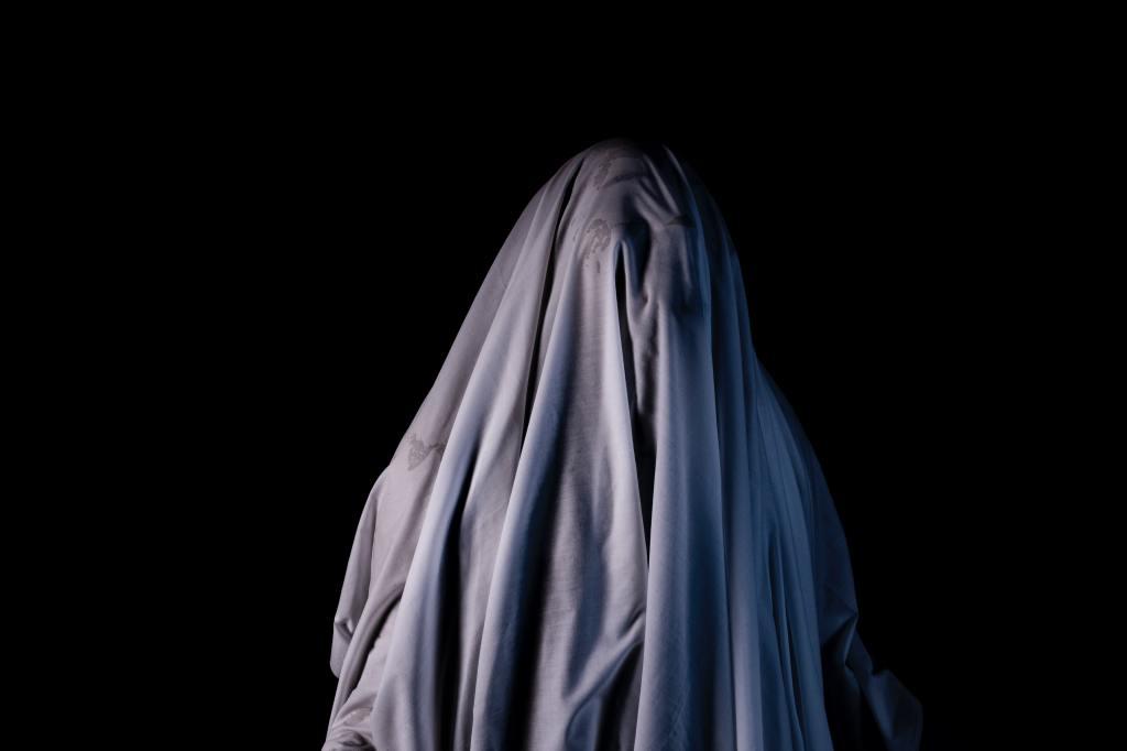 Schwarzer Hintergrund, davor eine gesichtslose Gestalt unter einem Falten werfenden hellgrauen Tuch.
