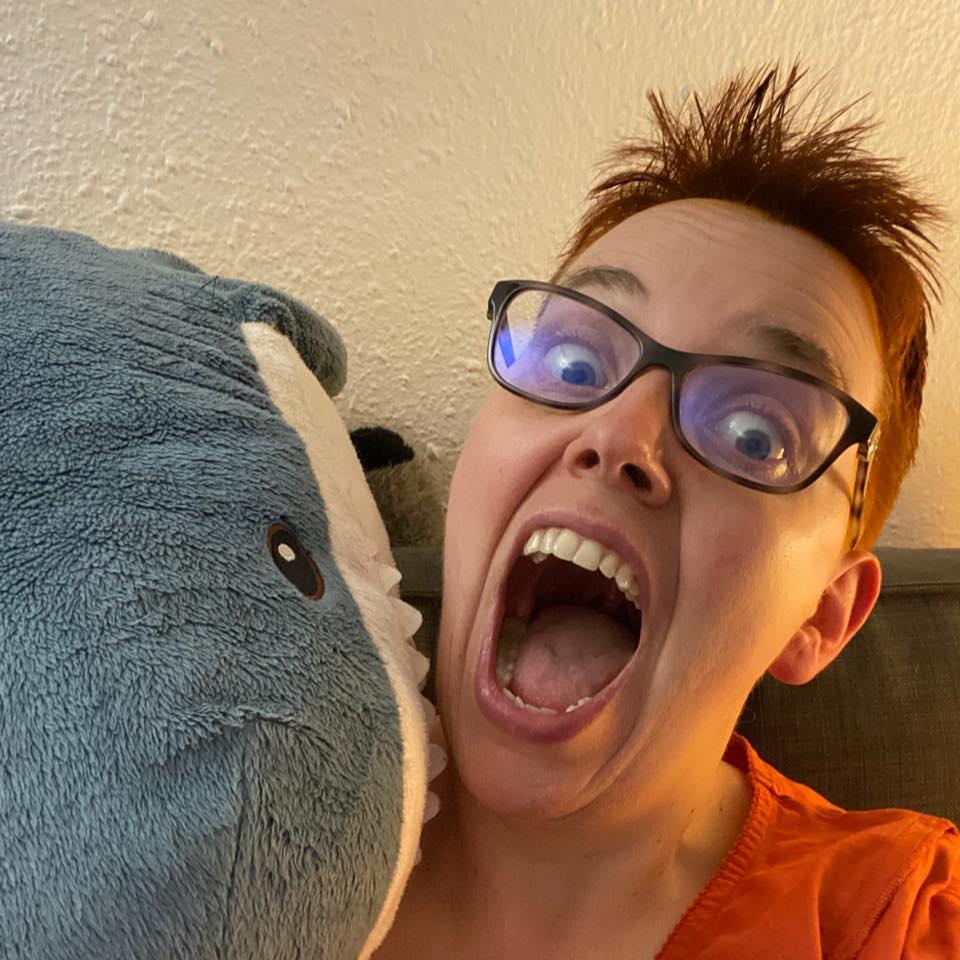 Schreiende Autorin wird von gigantischem Plüsch-Hai angefallen. Großaufnahme.