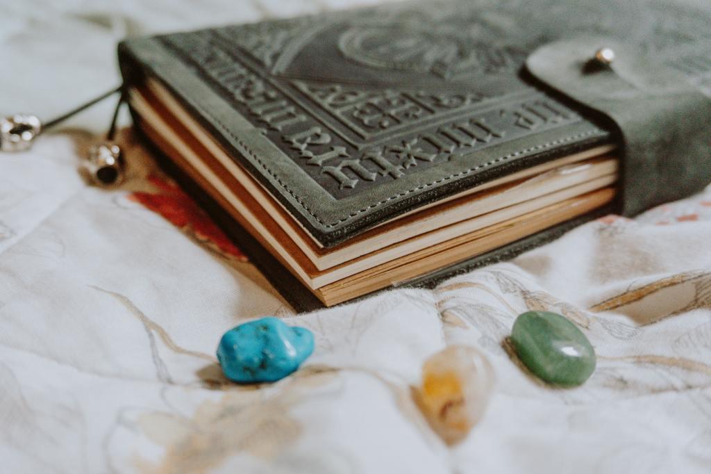 Auf einem hellen Stoff-Untergrund liegt ein in geprägtem LEder gebundenes Notizbuch. Im Vordergrund sieht man drei Halbedelsteine.