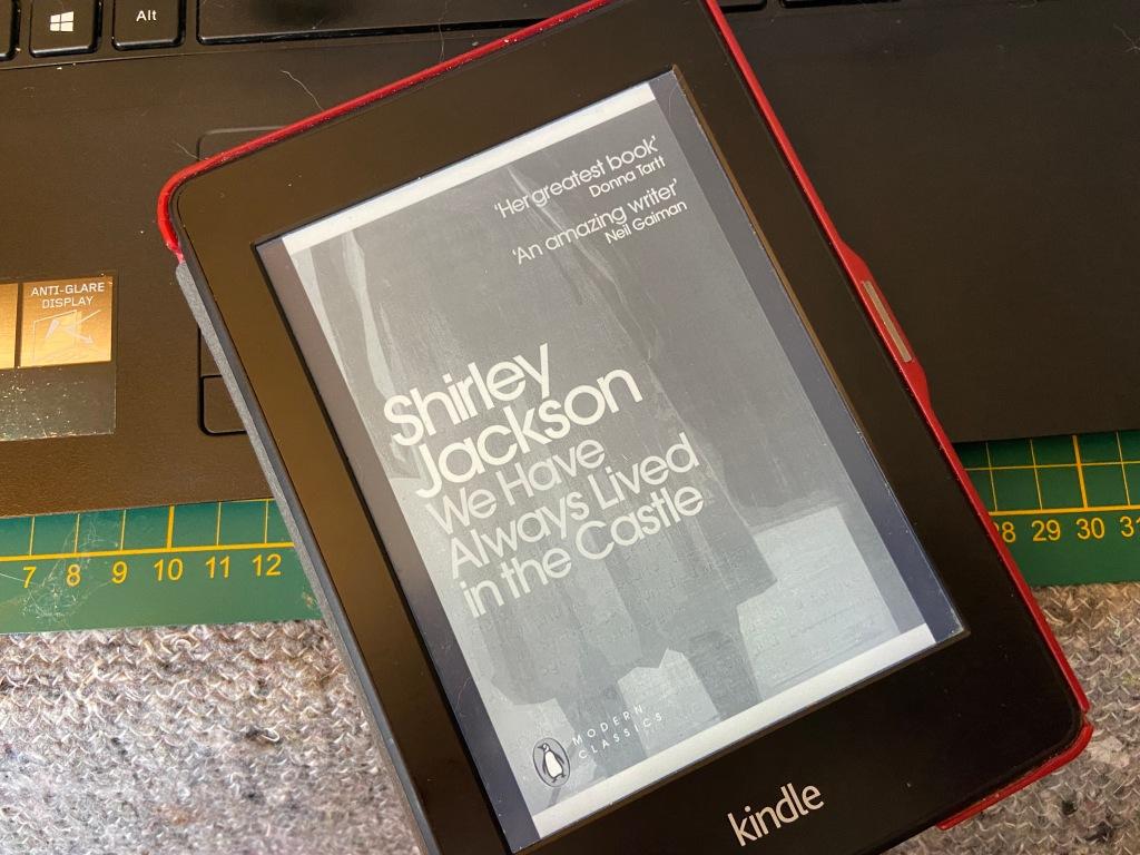 """Foto eines Kindle-E-Readers. Anzeige: Cover von """"We hav always lived in the Castle"""" von Shirley Jackson."""